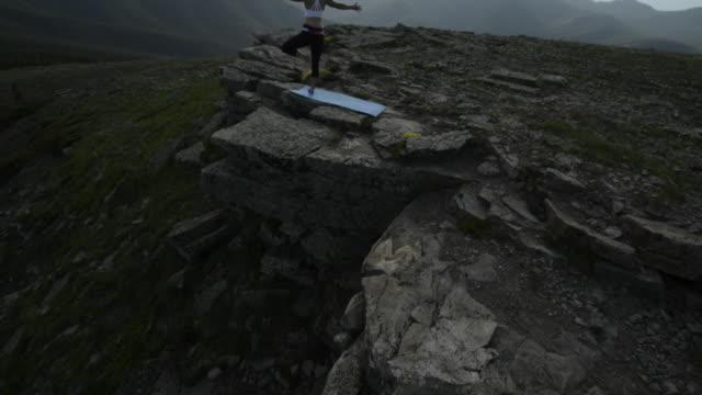 pan up to woman performing yoga on ridgecrest, above mtns - auf einem bein stock-videos und b-roll-filmmaterial