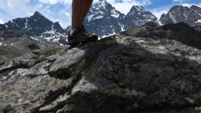 vidéos et rushes de pan up to young man checking compas in the mountains - seulement des jeunes hommes
