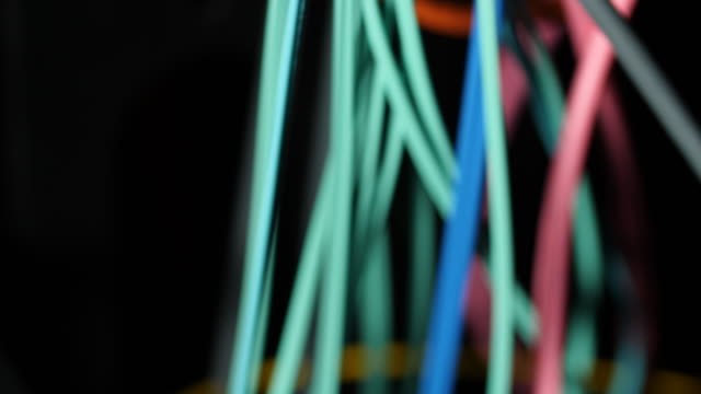 Pan up various coloured cables in a computer server room.