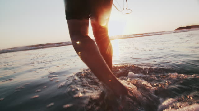pan up young man walking into the sea at sunset - swimming goggles stock videos & royalty-free footage
