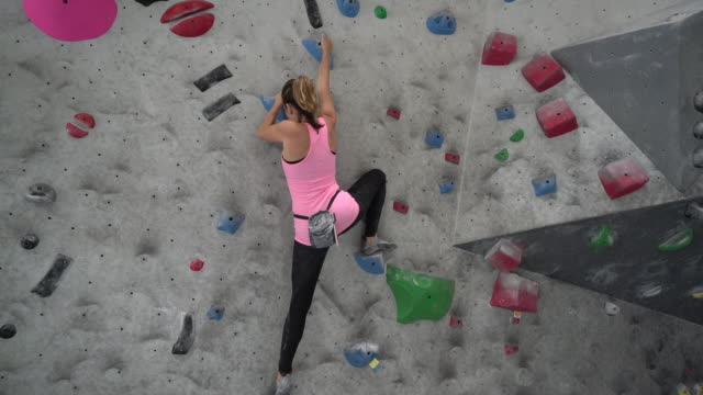 ws sm pan up young woman climbing a climbing wall - kletterwand kletterausrüstung stock-videos und b-roll-filmmaterial
