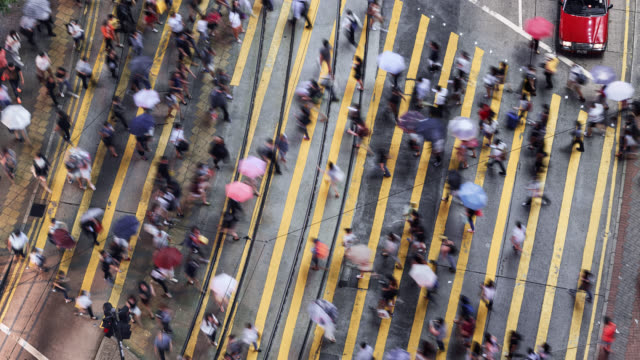 tl/pu-pd pan up/pan down time lapse of people and commuters crossing pedestrian crossing in central hong kong, aerial view - hong kong stock videos & royalty-free footage