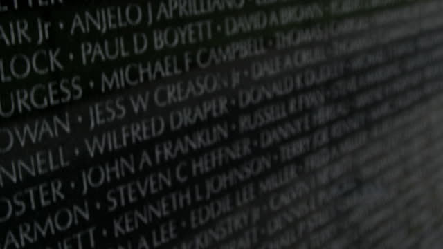 pan upward: remembering names of fallen soldiers (shot on red) - vietnam veterans memorial video stock e b–roll