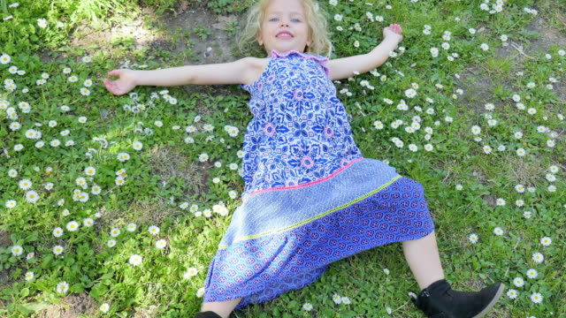 pan upward: small girl playing on a bed of flowers - lawn stock videos & royalty-free footage