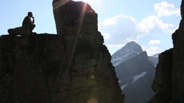 Pan upwards to businessman staring at rock pinnacle