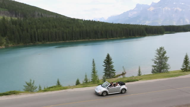 pan view of four teens driving convertible on mtn road - cabrio stock-videos und b-roll-filmmaterial