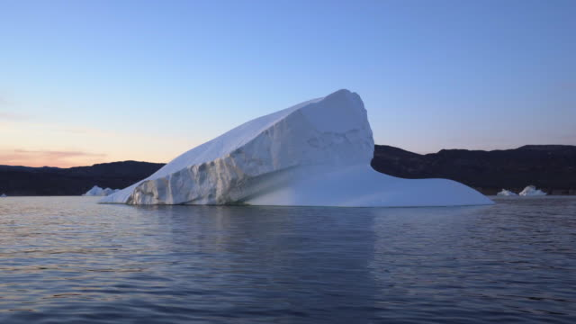 pan: white frozen iceberg in inlet during sunset against sky - disko bay, greenland - inlet stock videos & royalty-free footage
