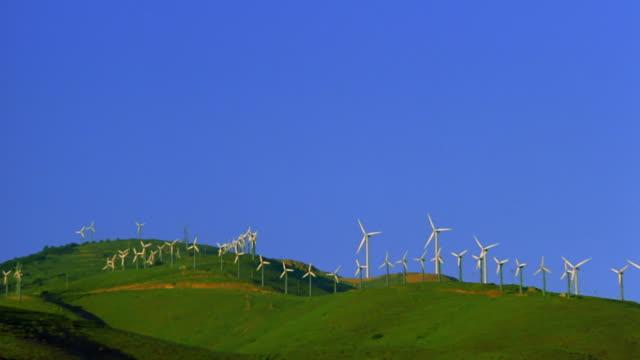 stockvideo's en b-roll-footage met pan wide shot wind turbines on rolling green hills with blue sky / tehachapi pass, californai - heuvel