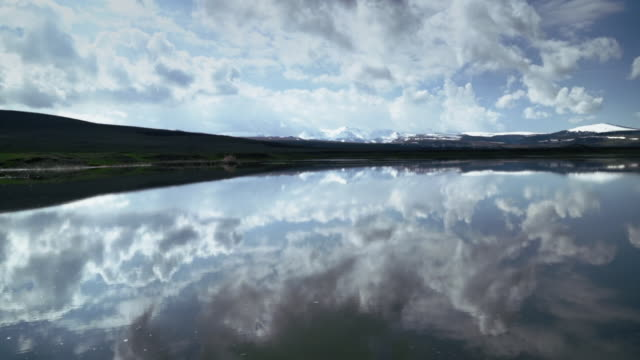 pan wide-angle shot of small pond with reflecting clouds in eastern anatolia. - anatolia stock videos and b-roll footage