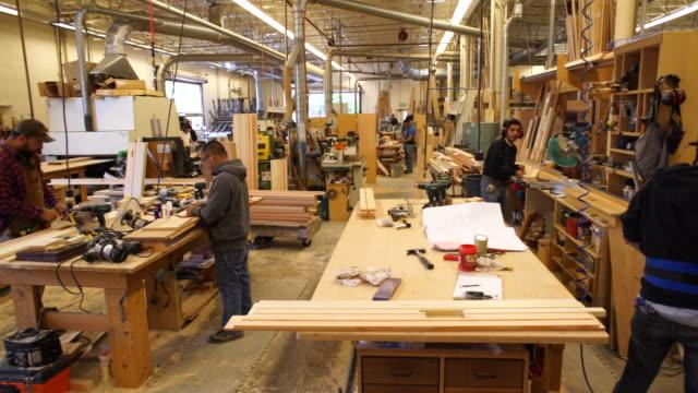 vídeos de stock e filmes b-roll de ws pan woodworking shop as workers enter and exit frame - protetor de ouvido
