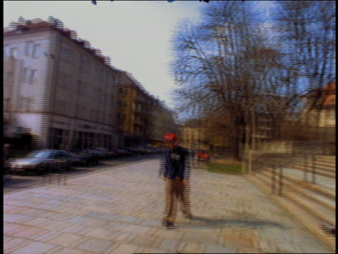 pan young man rollerblading towards camera on sidewalk / munich, germany (flash frames) - solo uomini di età media video stock e b–roll