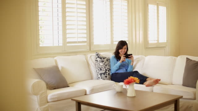 pan ws young woman playing on her phone at home. - 前ボケ点の映像素材/bロール