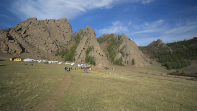 vídeos de stock e filmes b-roll de pan: yurts and structures with tourists walking on land by rocky mountains against sky - ulaanbaatar, mongolia - ulan bator