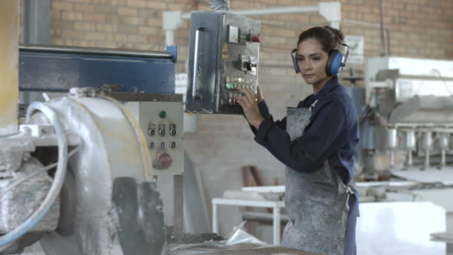 MS PAN_Female factory worker, operating stone cutting machine