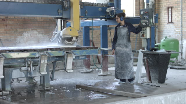 ws pan_female worker operating stone cutting machine, at factory - handhaben stock-videos und b-roll-filmmaterial