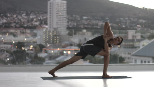 ws pan_man doing yoga exercises, in rooftop studio - yoga stock videos & royalty-free footage