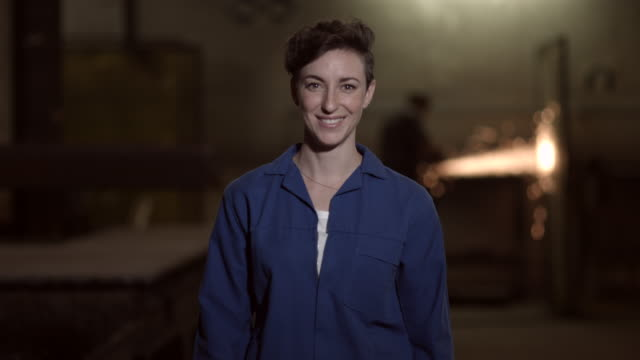 ms pan_portrait of female worker at steel plant, coworker welding in the background - short hair stock videos & royalty-free footage