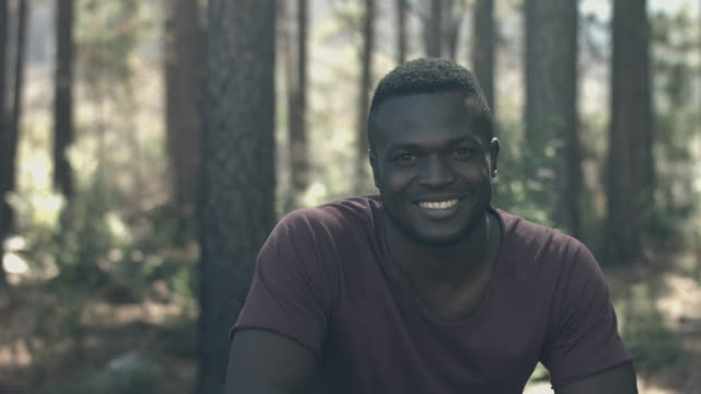 ms pan_portrait of young man on a hike in the forrest, smilling to camera - handsome people stock videos & royalty-free footage