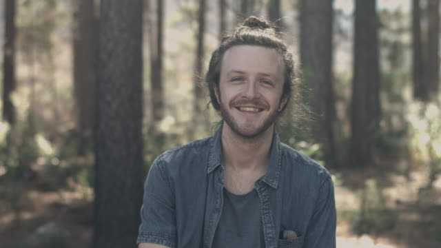 ms pan_portrait of young man on a hike in the forrest, smilling to camera - zona arborea video stock e b–roll