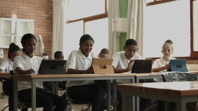 vídeos y material grabado en eventos de stock de ws pan_school kids in classroom, using digital tablets - camisa de polo