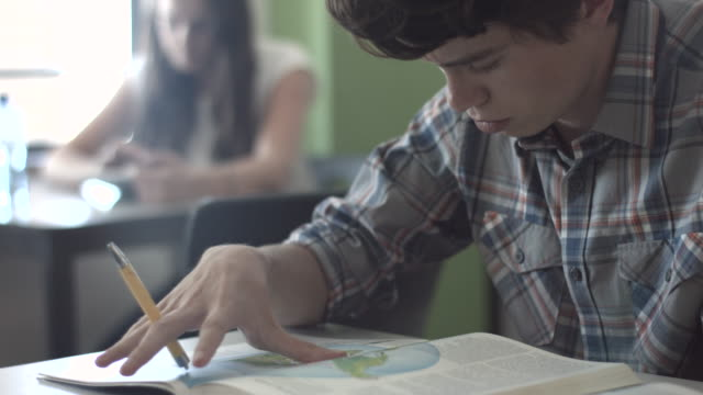 stockvideo's en b-roll-footage met cu pan_student reading book in classroom - fysische geografie