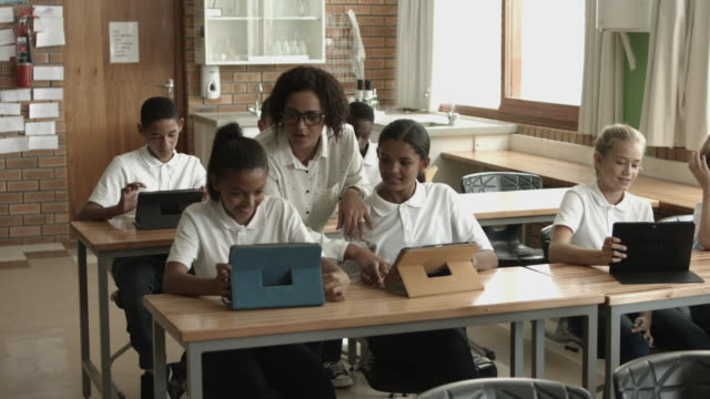 ws pan_teacher assisting students with digital tablets - uniform stock videos & royalty-free footage