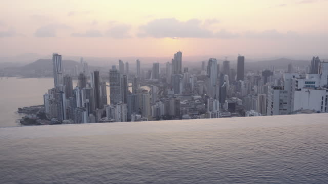 Panama city skyline at sunset. Fancy pool on the foreground. Lookout from a vantage point. Lights of the