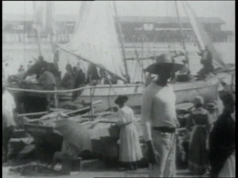 panama village with people in traditional dress walking around and working by the canal and coming to and from the boats carrying baskets and other... - anno 1906 video stock e b–roll