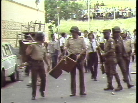 panamanian soldiers and civilians carry furniture along a panama city street. - パナマ点の映像素材/bロール