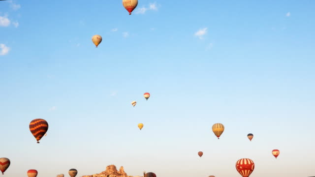 panaromic view of hot air balloon flying over the fairy chimneys with background uchisar castle at cappadocia - cappadocia stock videos and b-roll footage
