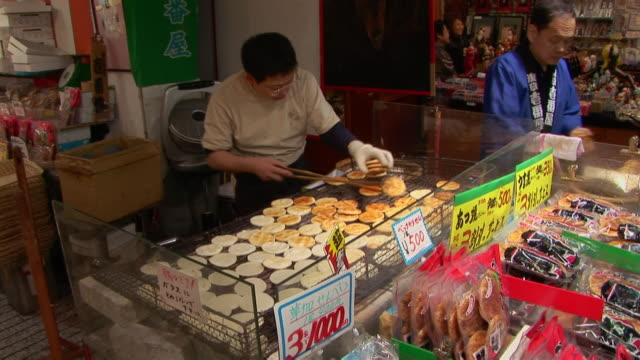 pancake vendor flipping pancakes on grill at nakamise street pedestrian mall / tokyo - retail place stock videos & royalty-free footage