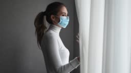 Pandemic Coronavirus. Covid 19 all over the world. A young woman in a disposable medical mask looks out the window. Life in quarantine and self-isolation.