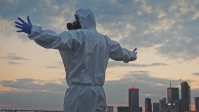 パンデミックユーモア。屋上でamrsを開くきれいなスーツを着た男 - クリーンスーツ点の映像素材/bロール