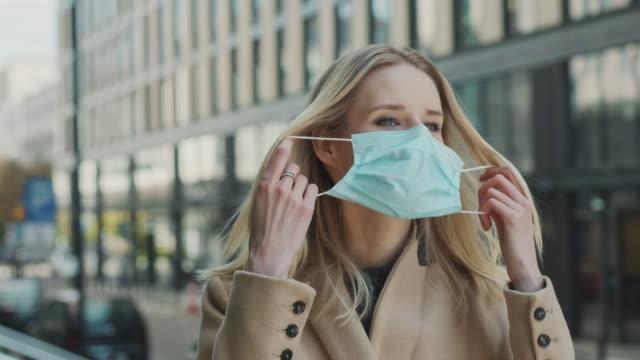パンデミックは終わった。マスクを脱いで深呼吸する女性 - 脱ぐ点の映像素材/bロール