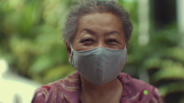 pandemic season : asian senior woman in a protective mask. - tradition stock videos & royalty-free footage