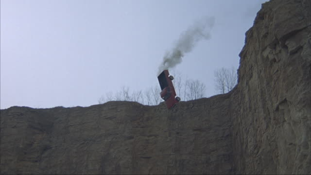 Pan-down as a red pickup truck shoots out over a cliff and lands on a quarry floor.