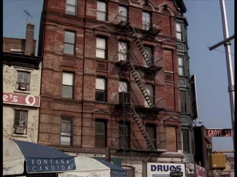 pan-down on an old red brick apartment building and pedestrians walking across the street below. - brick stock videos & royalty-free footage