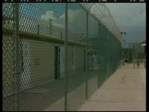 pandown shot of the barbed wire fence that separates guards and detainees at the camp delta section of guantanamo bay - crime or recreational drug or prison or legal trial stock-videos und b-roll-filmmaterial