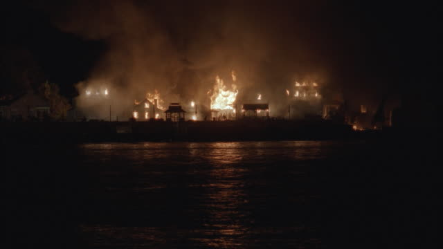 WS, Panic in burning western town at night, view from water towards land