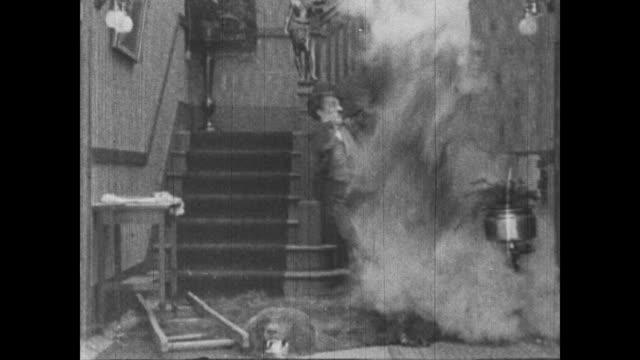1915 panicked charlie chaplin runs downstairs and bursts in on shooting scene and causes explosion - 無声映画点の映像素材/bロール