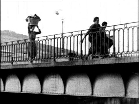 panicking people running on city street / woman carrying child and running on sidewalk / cu man inserting cartridge into machine gun / people running... - 撃つ点の映像素材/bロール