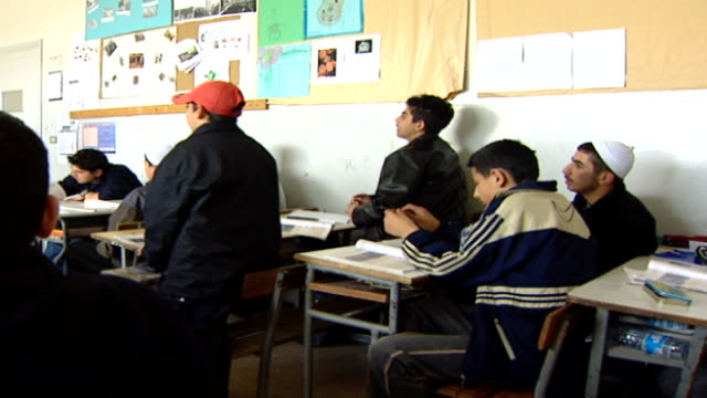 pan-left from the back of a classroom to a druze sheikh teacher lecturing schoolboys at irfan, a druze religious school with five branches across... - シャイフ点の映像素材/bロール