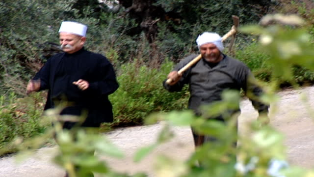 pan-left of a druze sheikh and a druze farmer walking down a rural road. the druze are a monotheistic esoteric ethnoreligious group who self-identify... - axe stock videos & royalty-free footage
