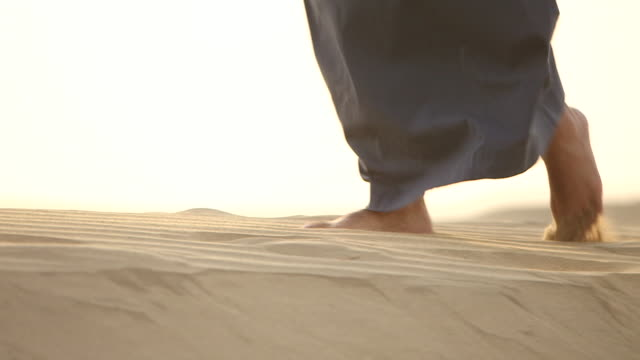 pan-left of the feet of a saudi man walking barefoot across a sand dune in the desert. - sand stock videos & royalty-free footage