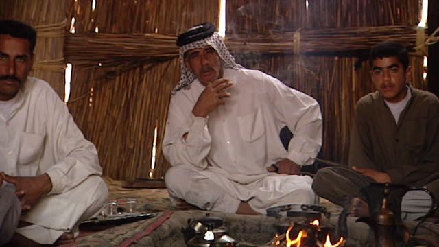 pan-left on iraqi marsh arab villagers sitting around an open fire in a traditional village mudhif . mudhif architecture dates back to sumerian times. - baghdad stock videos & royalty-free footage