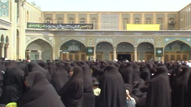 vidéos et rushes de pan-left over women in chador listening to a man lamenting over a loudspeaker at funerary rite in the fatima masumeh shrine. - vêtement religieux
