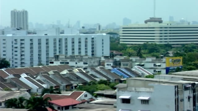 panleft view of the city showing the juxtaposition of crowded modern infrastructure and the lush vegetation of a temple compound - landscaped stock videos & royalty-free footage