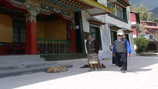 pan-left with tibetans circumambulating the library of tibetan works, carrying prayer beads and a prayer wheel. the library holds over 80000... - traditionally tibetan stock videos & royalty-free footage
