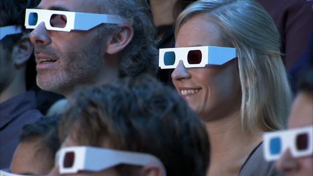 Pannig close-ups of audience members wearing 3-D glasses laughing, watching movie out of frame