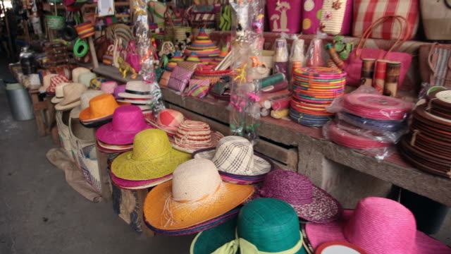 pannig view of street market with colorful hats and handbags. - 帽子点の映像素材/bロール